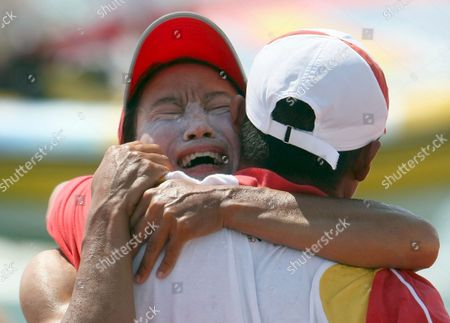 Yin Jian of China Celebrates Her Gold Medal Hugging a Chinese Olympic Team Official Her Gold Giving China Its First Ever Olympic Sailing Gold in the Womens Rs:x Women's Windsurfing Event in Qingdao China 20 August 2008 Italys Alessandra Sensini Won the Silver Medal and Bryony Shaw of Great Britain Won Bronze