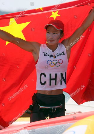 Yin Jian of China Celebrates Her Gold Medal Holding the Chinese Flag Giving China Its First Ever Olympic Sailing Gold in the Womens Rs:x Women's Windsurfing Event in Qingdao China 20 August 2008 Italys Alessandra Sensini Won the Silver Medal and Bryony Shaw of Great Britain Won Bronze
