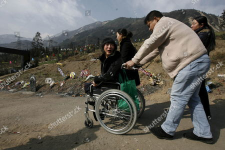 Stock Photo of Yang Lan 30-year-old Who Lost Her Legs During the Sichuan Earthquake in May 2008 Sits in a Wheelchair Pushed by Relatives On the Way to Sacrifice Her Dead Husband Ahead of the Chinese Lunar New Year in Yingxiu Town in Southwest China's Sichuan Province 24 January 2009 Many Locals Will Spend Their Upcoming Chinese Lunar New Year in Sichuan Earthquake Area Which Will Fall On 26 January 2009 According to the Chinese Lunar Calendar the Year of the Ox the China's Sichuan Earthquake Happened On 12 May 2008 with the 8 0 Magnitude According to Chinese State Officials the Quake Caused 69 181 Known Deaths Including 68 636 in Sichuan Province; 18 498 People Are Listed As Missing and 374 171 Injured But These Figures May Further Increase As More Reports Come in