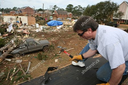 Mike Stokes of Lincoln Nebraska Hammers a Nail On His Mother's Damaged Roof in Enterprise Alabama Saturday 03 March 2007 Stokes Mother's Home Was Damaged But not Destroyed Unlike Her Neighbor's Home in the Background