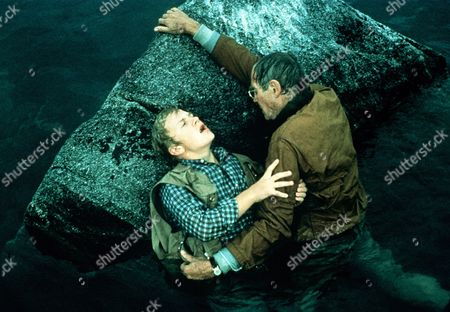 'On Golden Pond' Film - 1981 -  Norman Thayer, as played by Henry Fonda, tries to help the injured Billy Ray, as played by Doug McKeon, as they cling on to a rock in the pond.
