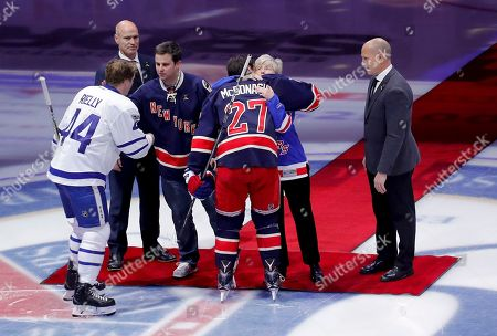 Patricia McDonald, second from right, hugs New York Rangers defenseman Ryan McDonagh (27) as her son New York City Police Sgt. Conor McDonald, shakes hands with Toronto Maple Leafs defenseman Morgan Rielly (44) as former Rangers Mark Messier, left, and Adam Graves watch before an NHL hockey game between the Rangers and the Toronto Maple Leafs, in New York. The McDonalds are the widow and son of NYPD Det. Steven McDonald, a long time Rangers fan, who died Tuesday. The detective was known for publicly forgiving a teenage gunman who in 1986 left him paralyzed from the neck down