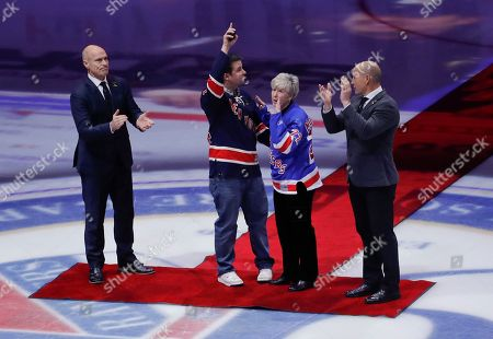 Patricia McDonald, second from right, and her son New York City Police Sgt. Conor McDonald wave to the crowd as former New York Rangers players Mark Messier, left, and Adam Graves watch before an NHL hockey game between the Rangers and the Toronto Maple Leafs, in New York. The McDonalds, who dropped the ceremonial first puck, are the widow and son of NYPD Det. Steven McDonald, a long time Rangers fan, who died Tuesday. The detective was known for publicly forgiving a teenage gunman who in 1986 left him paralyzed from the neck down