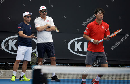 Japan's Kei Nishikori, right, prepares to hit the ball as his coaches Michael Chang, left, and Dante Bottini, second left, confer during a practice session at the Australian open tennis championship in Melbourne, Australia