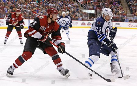 Winnipeg Jets right wing Blake Wheeler (26) pulls the puck away from Arizona Coyotes defenseman Oliver Ekman-Larsson (23) during the second period of an NHL hockey game, in Glendale, Ariz. The Coyotes defeated the Jets 4-3