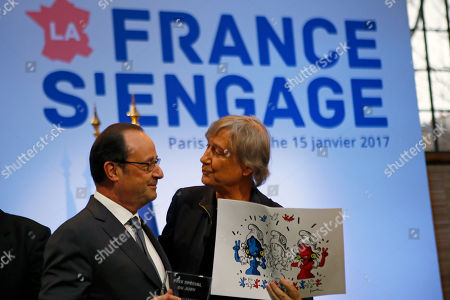 """French President Francois Hollande, left, receives a cartoon from French cartoonist Plantu of the """"Cartooning for Peace"""" association during a visit at a forum entitled """"La France s'engage"""" dedicated to associations for social and solidarity projects of education, employment, culture, environment and sports in Paris, France"""