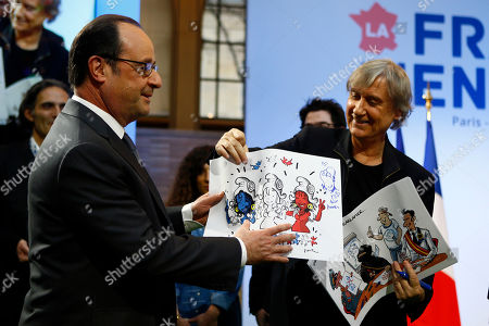 """French President Francois Hollande receives a cartoon from French cartoonist Plantu of the """"Cartooning for Peace"""" association during a visit at a forum entitled """"La France s'engage"""" dedicated to associations for social and solidarity projects of education, employment, culture, environment and sports in Paris, France"""