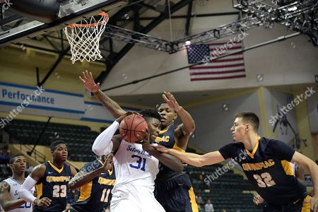 Seton Hall forward Angel Delgado (31) grabs a rebound in front of Quinnipiac guard Daniel Harris (23), forward Alain Chigha (11), forward Chaise Daniels and guard Peter Kiss (32) during the first half of an NCAA college basketball game at the AdvoCare Invitational tournament in Lake Buena Vista, Fla