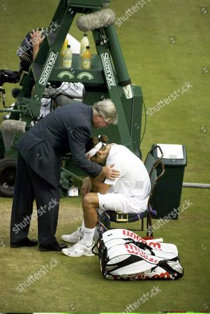 Defending Champion Roger Federer of Switzerland is Comforted by Referee Alan Mills After Defeating Andy Roddick of the Us in Their Men's Singles Final On Centre Court at the All England Lawn Tennis Championships in Wimbledon Sunday 04 July 2004 Federer Won the Match 4-6 7-5 7-6 6-4 to Claim the Championship Title For a Second Year Running