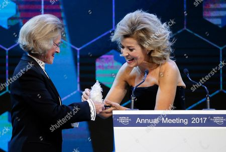 German violinist Anne-Sophie Mutter, right, receives a 'Crystal Award' by Hilde Schwab, left, wife of WEF founder Klaus Schwab, during a ceremony on the eve of to the World Economic Forum in Davos, Switzerland