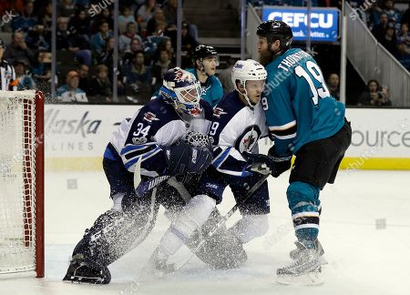San Jose Sharks' Joe Thornton (19) clashes with Winnipeg Jets' Toby Enstrom (39) and goalie Michael Hutchinson during the second period of an NHL hockey game, in San Jose, Calif