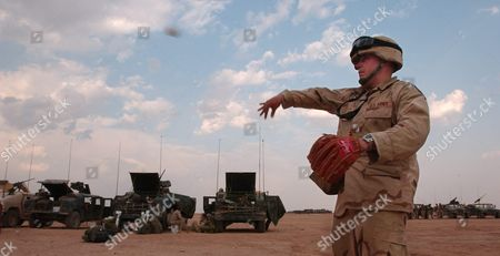 Private First Class James Peterson of Bemidji Minnesota Plays Catch at a Military Base Near Najaf Iraq On Monday 12 April 2004 Troops Comprising Task Force Duke Have Massed Outside Najaf and Are Awaiting Permission Pending Negotiations to Enter the City to Seek and Destroy the Mehdi Army and Its Leadership the Mehdi Army is Lead by Firebrand Shiite Cleric Moqtada Al Sadr