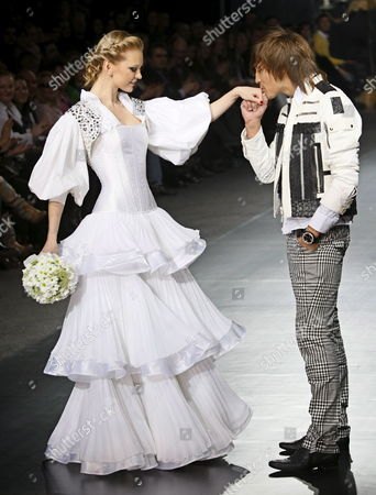 Winner of the Eurovision Song Contest 2008 Russian Singer Dima Bilan (r) Kisses the Hand of a Model As They Display Creations by Russian Designer Ilya Shiyan at the Fashion Week in Moscow Russia 23 March 2009 the Fashion Week Runs Until 27 March