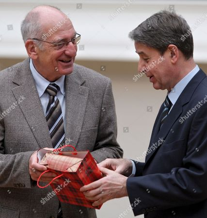Stock Picture of Swiss Federal Minister of the Interior and Culture Pascal Couchepin (l) and Alexander Avdeev (r) Minister of Culture of the Russian Federation Exchange Presents During Their Meeting in Tretikov's Gallery in Moscow Russia 01 March 2009
