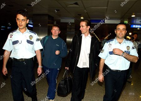Keith Kirkkom (2l) and Paul Ryder (2r) Two English Soccer Fans Whom Turkish Authorities Suspect May Have Planned to Incite Violence During the English Team's Arrival at Ataturk Airport in Istanbul Leave the Airport Escorted by Turkish Police Officers On Thursday 09 October 2003 Turkey Will Face England On 11 October at Fenerbahce Sukru Saracoglu Stadium in Istanbul in the Last Match of Their Group England Leads the Group One Point Ahead of Turkey