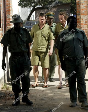 British Journalists Julian Simmons (r) and Toby Harnden Are Escorted by Prison Officers Into the Court in Legirons Before They Were Granted Bail in Norton Zimbabwe 40 Kilometers (25 Miles) West of Harare Wednesday 13 April 2005 the Two Journalists Working For British Broadsheet the Sunday Telegraph Were Arrested After They Were Caught Allegedly Covering Pre-election Activities in Zimbabwe Without Accreditation