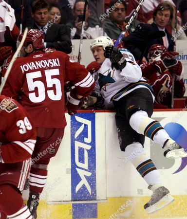 Phoenix Coyotes Head Coach Wayne Gretzky (r) Looks On As San Jose Sharks Jeremy Roenick is Checked Into the Bench Area by Ed Jovanovski (l) During the First Period in Glendale Arizona Usa On 10 January 2008