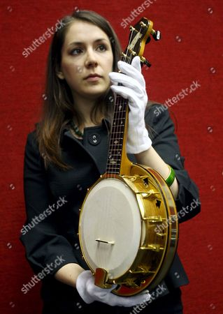 A Bonham's Auction House Staff Holds a Banjolele Once Owned by George Formby and Later George Harrison at Bonham's Auction House in London Britain 12 June 2008 the Banjolele is Expected to Fetch 30 000-40 000 Euros at Auction 18 June