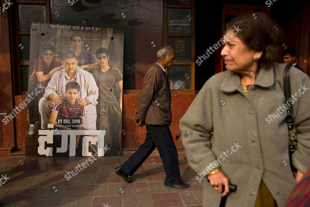 An elderly man walks past a poster of Bollywood movie Dangal, a 2016 Bollywood biopic on an Indian wrestling coach and his two professional wrestler daughters, outside a theater in New Delhi, India, . The 16-year old actress of the film Zaira Wasim, who played the part of the older sister and Commonwealth Games gold medalist Geeta Phogat, has recently been criticized over her meeting with the chief minister of Jammu and Kashmir state. Several people from the film industry have spoken up in her support