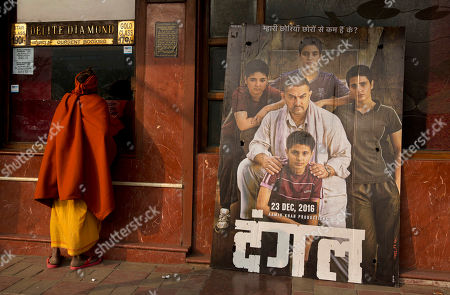 An Indian Sadhu, or Hindu holy man, buys a movie ticket at a counter beside a poster of Bollywood movie Dangal, a 2016 biopic on an Indian wrestling coach and his two professional wrestler daughters, outside a theater in New Delhi, India, . The 16-year old actress of the film Zaira Wasim, who played the part of the older sister and Commonwealth Games gold medalist Geeta Phogat, has recently been criticized over her meeting with the chief minister of Jammu and Kashmir state. Several people from the film industry have spoken up in her support