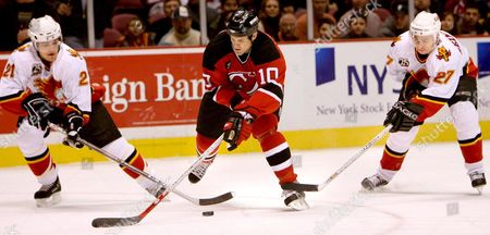 Stock Picture of Devils' Player Erik Rasmussen (c) Drives Through Flames Andrew Ference (l) and Steven Reinprecht (r) During the First Period of the Calgary Flames' Game Against the New Jersey Devils at Continental Airlines Arena Wednesday 07 December 2005 in East Rutherford New Jersey