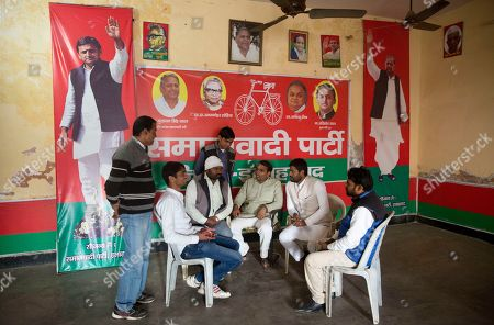 Samajwadi Party (SP) workers sit by banners showing party leader and Chief Minister of Uttar Pradesh state Akhilesh Yadav, left, and his father and party founder Mulayam Singh Yadav, right, at the party office in Allahabad, India, . Elections in the state will be held over seven phases beginning Feb. 11