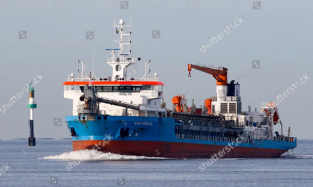 Stock Image of German Hopper Dredger 'Eke Moebius' steams off after unloading on the Elbe river near Cuxhaven, northern Germany, 17 January 2017. Several dredging ships are deployed to clear the shipping routes towards the port of the city of Hamburg upstream the Elbe River.