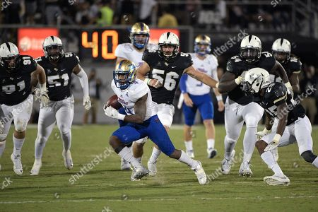 Tulsa running back D'Angelo Brewer (4) rushes for yardage in front of Central Florida defensive lineman Joey Connors (91), linebacker Errol Clarke (51), linebacker Pat Jasinski (56) and defensive back Kyle Gibson (25) during the first half of an NCAA college football game on in Orlando, Fla
