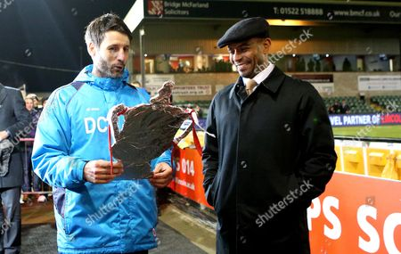 Lincoln City manager Danny Cowley holds a tin foil version of the FA Cup while he chats with BBC Pundit Trevor Sinclair