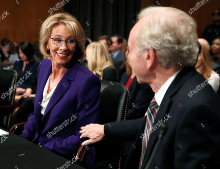 Education Secretary-designate Betsy DeVos talks to Joe Lieberman before testifying on Capitol Hill in Washington, at her confirmation hearing before the Senate Health, Education, Labor and Pensions Committee