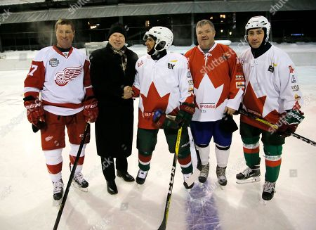 From left, Doug Brown, a two-time Stanley Cup winner, Mike Keenan, coach of the 1994 Stanley Cup winning team, Rustam Minnikhanov President of the Russian Republic of Tatarstan, match organiser Scotty Macpherson and coach of the President Nasibullin Lenar pose for a group photo prior to the hockey game just outside the World Economic Forum venue in Davos Switzerland, . The two teams tied 10-10