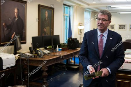 Secretary of Defense Ash Carter holds a Marine Corps Ka-Bar knife while being interviewed in his Pentagon office, in Washington. Carter said Wednesday he had opposed commuting the prison sentence of convicted leaker Chelsea Manning, who was convicted in 2013 of espionage and other crimes for leaking classified information while deployed in Iraq