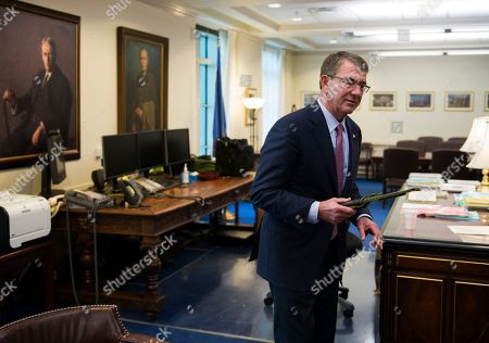 Secretary of Defense Ash Carter holds a Marine Corps Ka-Bar fighting knife while being interviewed in his Pentagon office, . The knife was given to him earlier in the day by his Senior Miltary Assistant Marine Brig. Gen. Eric Smith and was carried by Smith on all of his deployments. Sending thousands more American troops into Iraq or Syria in a bid to accelerate the defeat of the Islamic State group would push U.S. allies to the exits, create more anti-U.S. resistance and give up the U.S. military's key advantages, Carter said in an Associated Press interview