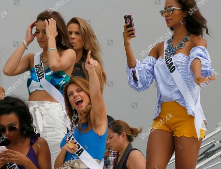 Cherell Williamson, Rebecca Rath, Hildur Maria, Chanelle de Lau Miss Universe contestant Carolina Duran of Costa Rica, center, reacts to a TV network's drone as others prepare to pose from the deck of the yacht Happy Life prior to cruising to a beach resort in Batangas province at the Philippine Navy headquarters in Manila, Philippines. Eighty-six candidates from around the world are vying for the title to succeed Pia Wurtzbach from the Philippines. The competition takes place on Jan. 30. They are, from left, Cherell Williamson of Bahamas, Rebecca Rath of Belize, Hildur Maria of Iceland, and Chanelle de Lau of Curacao