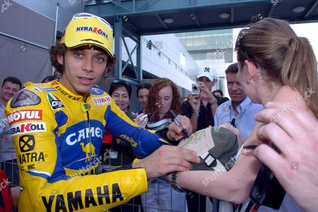 Italian Yamaha Motogp Rider Valentino Rosi (l) Signs Autographs After the Qualifying Practice at Lusail International Circuit On Friday 07 April 2006 Rosi Finished Sixth in Qualifying Grand Prix of Qatar Scheduled For Saturday 08 April