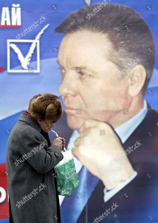 An Elderly Russian Man Passes by a Campaign Poster of the United Russia Party Decorated with a Portrait of Moscow Region's Governor Boris Gromov Thursday 04 December 2003 the United Russia is Known As Party of the Power and Contains in Its Electoral List 35 Governors