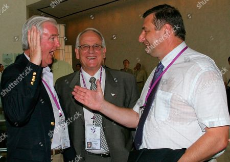 France's Sport Minister Jean-francois Lamour (r) Chats with French International Olympic Committee Member Henri Serandour (c) and an Unidentified International Olympic Committee Member in Singapore Monday 04 July 2005 Paris is Bidding to Host the 2012 Olympics Contending Against Cities New York Madrid Moscow and London the Ioc Will Formally Hear the Contending Citites Bids and Announce the Winner After Voting Wednesday in Singapore
