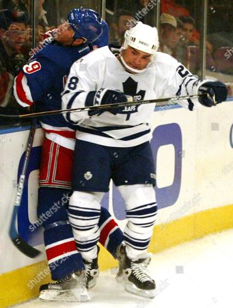 Toronto Maple Leafs' Tie Domi (r) Hip Checks New York Rangers' Dan Lacouture (l) Into the Boards Friday 26 December 2003 During Second Period Action of the Nhl Game in New York