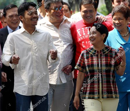 Filipino Boxing Hero Manny Pacquiao (l) Walks with Philippine President Gloria Macapagal-arroyo (r) at the Presidential Palace in Manila Philippines On 11 October 2007 Pacquaio Was Honoured After Beating Mexican Boxer Marco Antonio Barrera Last Weekend in Las Vegas Usa