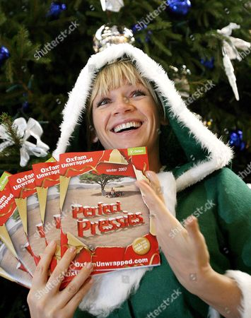 Stock Picture of Oxfam Ambassador Zoe Hall Holds Up Perfect Pressies Brochures at a Train Station in London Britain 29 November 2007 Hall is Campaiging to Encourage Britons to Spend Their Money Wisely This Christmas On Presents and Gifts For People in Afirca Who Really Need It