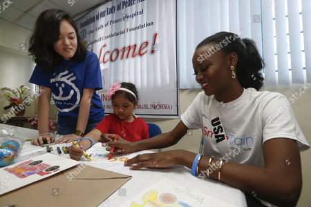 Miss Universe candidate Deshauna Barber from the USA (R) and a child beneficiary (C) of a charitable institution helping cleft patients, make colorful posters with messages for candidates, during a visit to the Our Lady of Peace Hospital in Paranaque City, south of Manila, Philippines 20 January 2017. A total of 86 candidates are vying for the 65th Miss Universe crown, with the coronation event scheduled for 30 January.