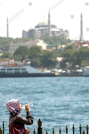 A Turkish Muslim Woman Drinks Water On the Banks of the 'Golden Horn' with an Overview of Hagia Sophia in Istanbul Turkey On 23 July 2007 Sunday's General Election in Turkey Resulted in Victory For the Turkey's Ruling Party Akp 'Justice and Development Party'