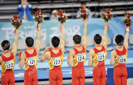 Chinese athletes Yibing Chen, Xu Huang, Xiaopeng Li, Qin Xiao, Wei Yang and Kai Zou celebrate with their Gold medals winning the men's team final at artistic gymnastics