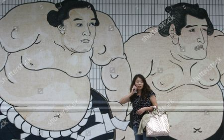 A Young Japanese Woman Stands Before a Wall Decorated with Sumo Wrestlers Paintings at the Kokugikan Sumo Arena in Tokyo Japan 25 May 2008 ?the Sumo History Opened a New Page As Bulgarian Kotooshu Became the First European Wrestler to Win the Emperor's Cup at a Grand Sumo Tournament
