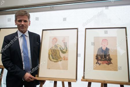 Austrian Federal Minister For Arts and Culture Constitution and Public Service Josef Ostermayer Poses Next to Nazi-looted Drawings by Austrian Artist Egon Schiele (1890-1918) During a Press Conference at the Leopold Museum in Vienna Austria 07 April 2016 the Museum and the Jewish Community Vienna Achieved an Agreement to Return the Two Drawings 'Sitzender Bub Mit Gefalteten Haenden' (lit: Sitting Boy with Folded Hands) From 1910 (r) and 'Selbstdarstellung Mit Gestreiften Aermelschonern' (lit: Self Portrait with Striped Sleeves Protectors) From 1915 (l) to the Heiress of Late Austrian Art Collector Karl Maylaender Three Other Drawings of the Collection of Maylaender Remain at the Leopold Museum Austria Vienna