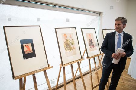 Stock Image of Austrian Federal Minister For Arts and Culture Constitution and Public Service Josef Ostermayer Poses Next to Nazi-looted Drawings by Austrian Artist Egon Schiele (1890-1918) During a Press Conference at the Leopold Museum in Vienna Austria 07 April 2016 the Museum and the Jewish Community Vienna Achieved an Agreement to Return the Two Drawings 'Sitzender Bub Mit Gefalteten Haenden' (lit: Sitting Boy with Folded Hands) From 1910 (r) and 'Selbstdarstellung Mit Gestreiften Aermelschonern' (lit: Self Portrait with Striped Sleeves Protectors) From 1915 (c) to the Heiress of Late Austrian Art Collector Karl Maylaender Three Other Drawings of the Collection of Maylaender Remain at the Leopold Museum Austria Vienna