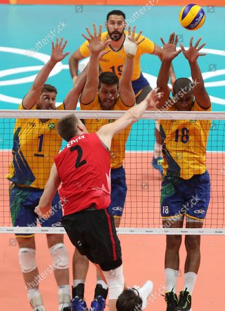John Gordon Perrin (front) of Canada in Action Against Bruno Mossa Rezende (l) Eder Carbonera (c) and Ricardo Lucarelli (r) of Brazil During the Men's Preliminary Round Volleyball Match Between Brazil and Canada of the Rio 2016 Olympic Games at Maracanazinho Indoor Arena in Rio De Janeiro Brazil 09 August 2016 Brazil Rio De Janeiro