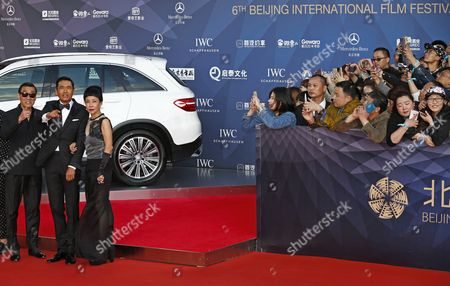 Stock Picture of (l-r) Hong Kong Actor Tony Leung Ka-fai Chinese Actor Chow Yun Fat and His Wife Jasmine React While Fans Photograph Them During the Opening Ceremony Red Carpet Event of the 6th Beijing International Film Festival at the Beijing Yanqi Lake International Convention and Exhibition Center in Beijing China 16 April 2016 the Film Festival Runs From 16 to 23 April China Beijing