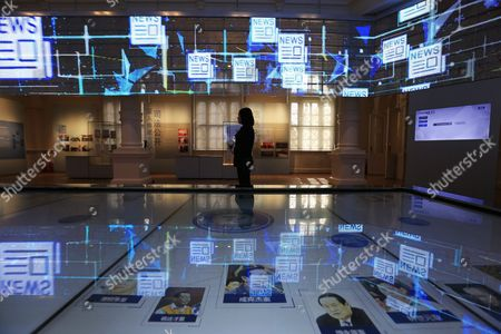 Stock Photo of A Woman Looks at the the Main Exhibition Hall of the China Court Museum where a a Picture of Former Chinese Security Chief Zhou Yongkang (bottom L) is Seen on an Interactive Touch Panel in Beijing China 22 January 2016 the China Court Museum Opened 06 January Showcasing the Country's Legal and Court System Over the Years Prominent on Display in the Main Hall Were Exhibits From Two of China's Most Politically Sensitive Trials of Former Security Chief Zhou Yongkang and Former Chongqing Communist Party Boss Bo Xilai Whose Dramatic Downfalls in Two Separate Unrelated Trials Gripped the Nation China Beijing