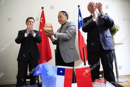 Director of the Chile-china Culture Institute Juan Carlos Ramirez (l) and Chilean Ambassador to China Jorge Heine (r) Applaud As Chinese Writer and 2012 Nobel Prize Winner in Literature Mo Yan (c) is Presented with a Gift During a Signing Ceremony at the Embassy of Chile in Beijing China 31 May 2016 Mo Signed an Agreement with Ramirez During the Ceremony to Adapt His Novel 'Life and Death Are Wearing Me Out' Into a Spanish Stage Play China Beijing